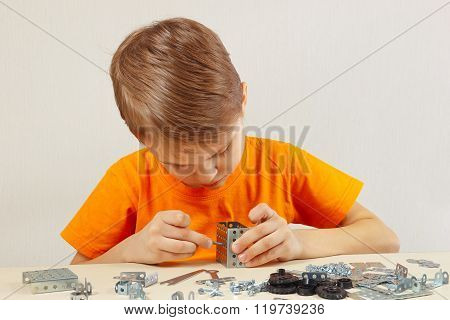 Little boy plays with metal constructor at table