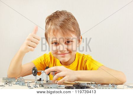 Young engineer plays with mechanical constructor at table