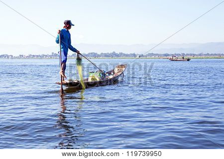 INLE LAKE, MYANMAR - November 15, 2015: Intha people possess the unique leg-rowing style on Inle Lake, Myanmar