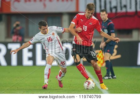 VIENNA, AUSTRIA - OCTOBER 12, 2014: Lukas Hinterseer (#19 Austria) and Vladimir Jovovic (#16 Montenegro) fight for the ball in an European Championship qualifying game.