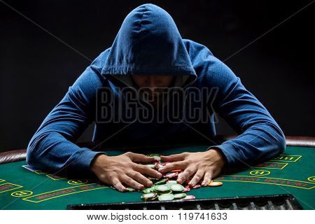 Poker player taking poker chips after winning