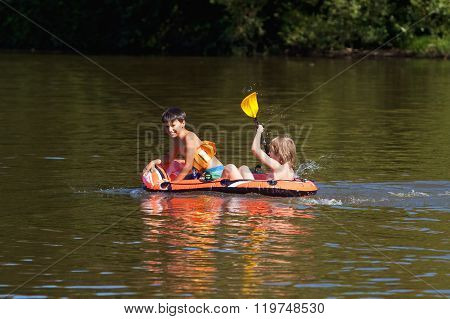 Two Boys Having Fun On Inflatable Rubber Boat