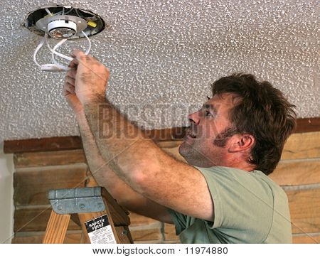 an electrician installing an overhead light and testing the switches. (focus is his face)