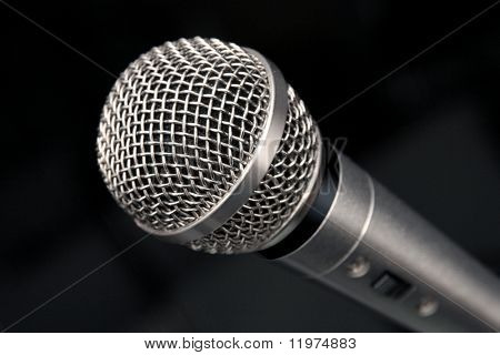 an extreme closeup view of a microphone on a black background