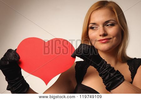 Beautiful young blonde woman holding red hart