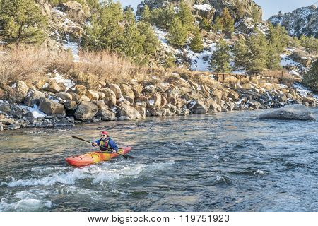 senior kayaker in a whitewater kayak paddling upstream - Arkansas River, Colorado in winter scenery