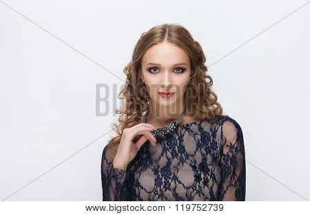 Young ironic blonde woman in blue dress with curly hairstyle touching her necklace