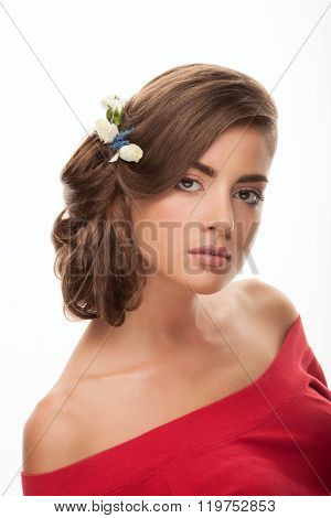 Young adorable brunette woman with low bun hairstyle, flower headpiece, and cute makeup posing with