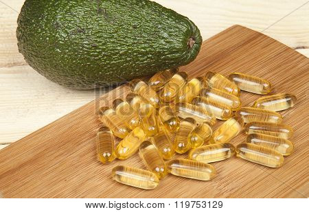 Cod liver oil omega 3 gel capsules with avocado on wooden background