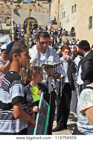 JERUSALEM, ISRAEL - OCTOBER 16, 2011:The Sacred Western wall of the Temple. The Jewish family - the father in religious clothes with the son and a daughter prays with the prayer book.