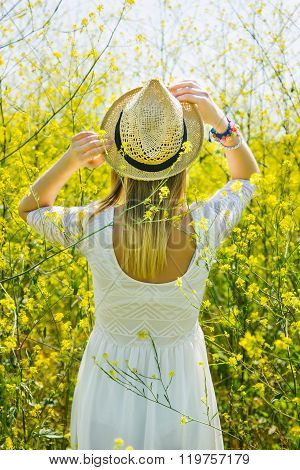 Girl in white dress in the field of yellow flowers, outdoor, hapiness, carefree concept