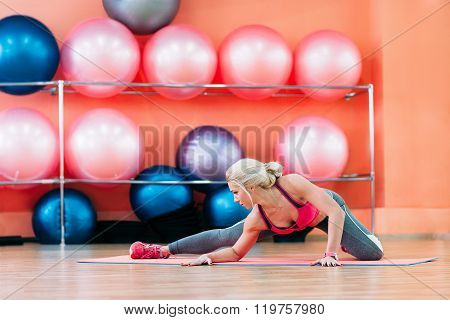young girl doing stretching in fitness studio