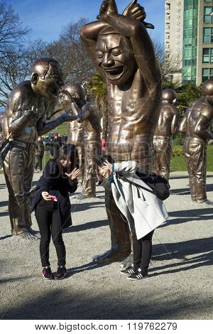 VANCOUVER-CANADA, 8 February 2016: Yue Minjun is part of Cynical Realism, Chinese artistic movement in response to 1989 demonstrations in Tiananmen. The bronze characters depict the artist's own face