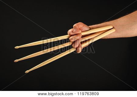 Hand With Three Drumsticks Over Black