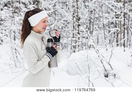 Woman Pours And Drinks Tea From A Thermos After Jogging