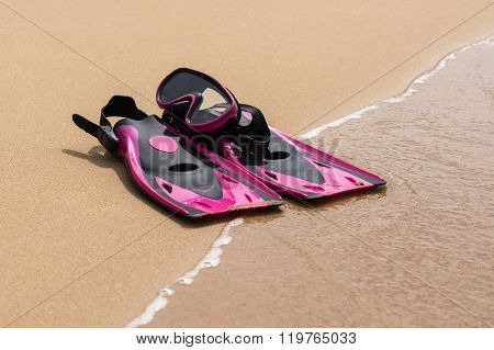 Pink Flippers On The Sand Of Beach With Wave On Background