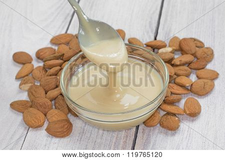 Teaspoon Of Almond Butter In A Glass Bowl With Almonds