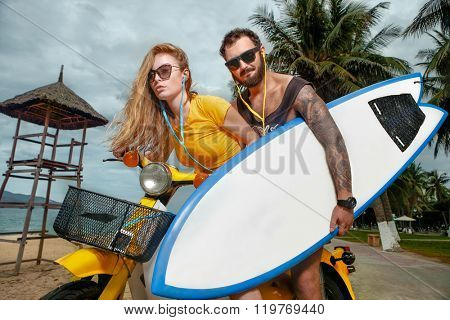 Portrait of glamorous young couple having fun with surf board on scooter