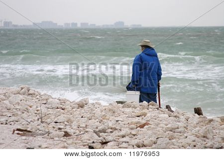 A senior woman, scavenging the beach for treasure as a storm rolls in across the water.