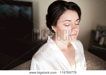 Bride with closed eyes showing bridal makeup in morning wearing white silk robe. Wedding preparation
