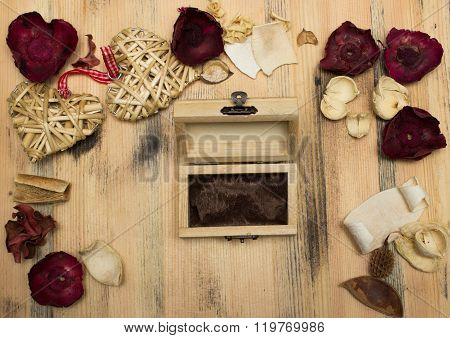 Gift box, heart and herbarium on wooden background