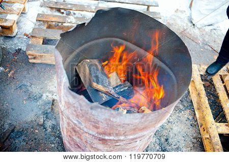 burning firewood in old empty barrel, outdoor