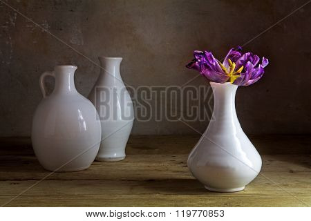 White Ceramic Vases With A Single Purple Tulip With Visible Stamens On A Rustic Wooden Table Against
