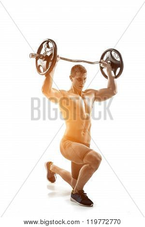 Muscular man standing on knee, holding barbell over his head