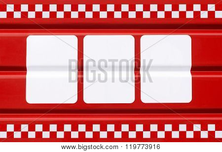 red metal plate with three white rectangles for symbols