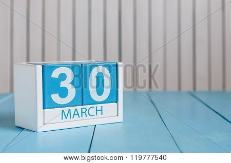 March 30th. Image of march 30 wooden color calendar on white background.  Spring day, empty space fo