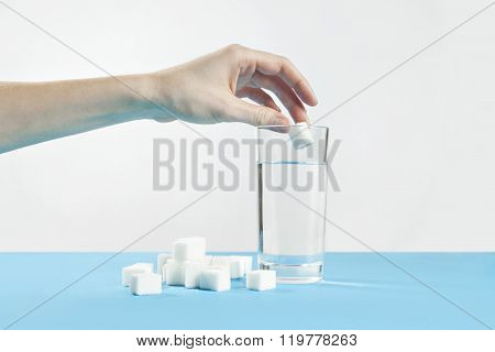 Glass of water against sugar, diabetes disease, sweet addiction, hand drop a sugar