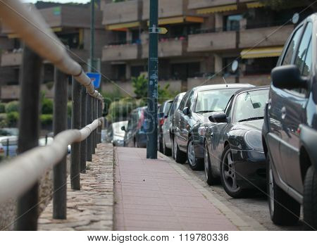 Row of parked cars leaving afar