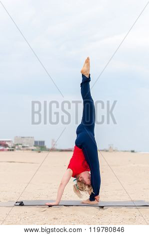 Sporty womang Supported Headstand, yoga asana on coast background