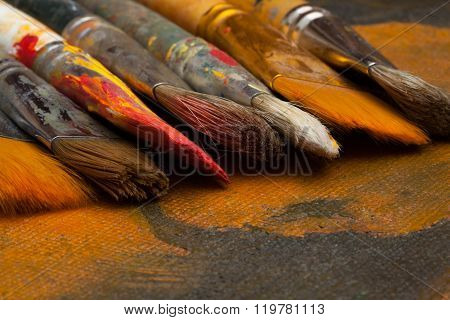 several artistic brushes against the background of the canvas