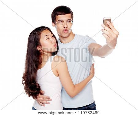 Young Interracial couple, hispanic man and asian girl, having fun making duckface and taking selfie on smartphone isolated on white background - humor concept