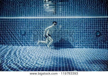 Man under water runs along the bottom of a swimming pool