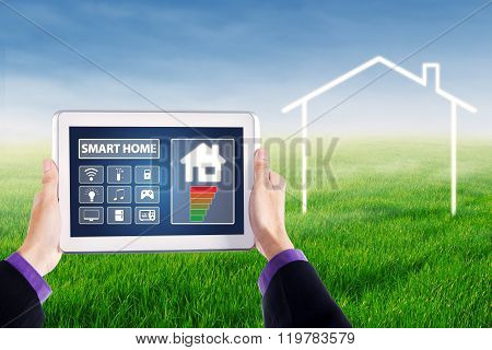 Hands Holding Smart House Controller At Field