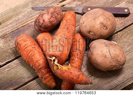 Vegetables, The Crude Carrots And Potatoes, Against From Gray Boards