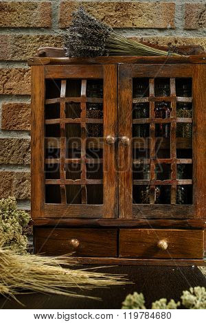 Farms vintage Spice Rack or Storage Cabinet: Wall Mount - Display Shelf Two Drawers Six Glass Bottles with lavender whole wheat and oregano on rural background village life