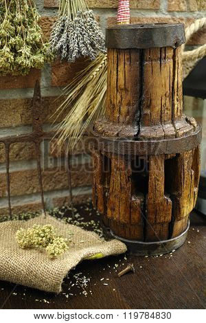Antique Pitchfork And Wooden Wheel Hub On Burlap Sack Against Rural Brick Wall