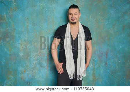Portrait of a young man in black slacks and a black T-shirt and white scarf hairstyle with shaved temples and slicked back hair at the head different emotions blue wall floor Brick wall beard