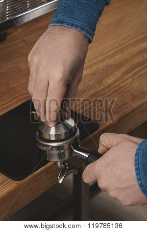 Barista Using Tamper To Press Ground Coffee Into Portafilter