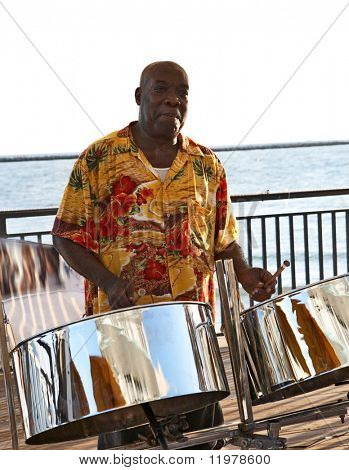 A caribbean musician playing steel drums.