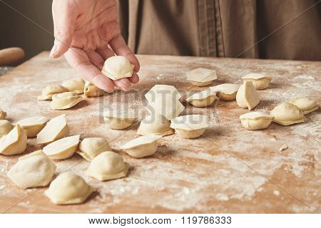 Woman Hand Holds One Ravioli Above Others On Wooden Boards