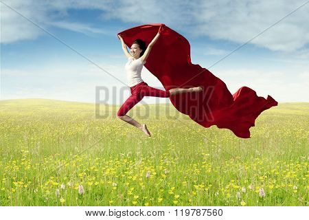 Woman Leaps At Field With Red Fabric