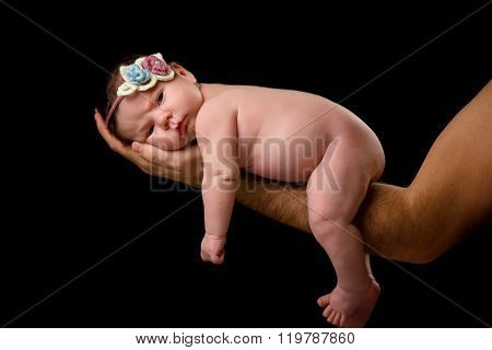 Newborn Baby Girl With Knitted Headband Lying In Father's Hands On A Black Background