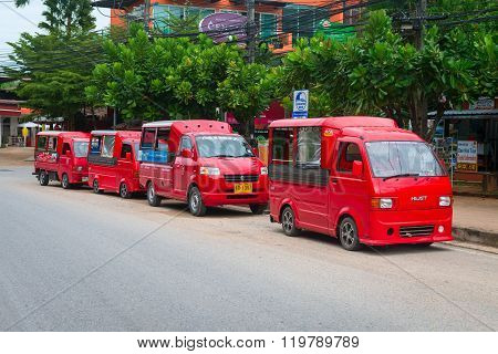 Four Red Taxis Parked In The Street.