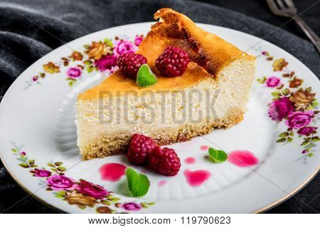 Cheesecake Slice With Raspberries And Mint Leaves On Plate.