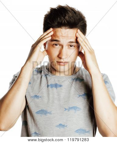 young pretty man with head ache holding hands isolated close up thinking