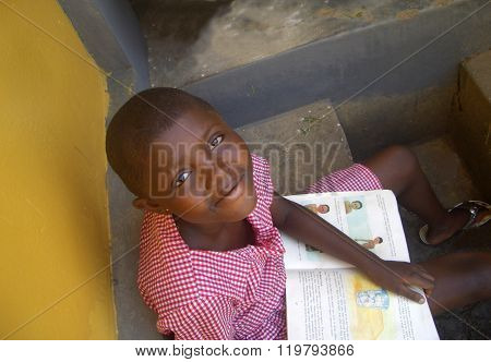 Student reading a textbook in Ghana